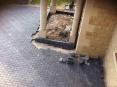 Charcoal block paved driveway meeting a curbrace around a portico to front of building