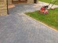 Kiln dried sand brushed into joints of block paving to strengthen bonding, then compressed