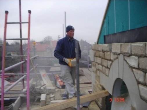 Stone mason ready to slot in the cut down stone above the featured stone arch