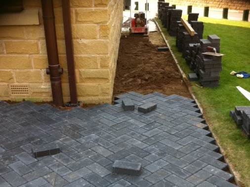 Continuation of a block paving patio area forming metre wide path ready for the ground to be compressed using the whacker plate